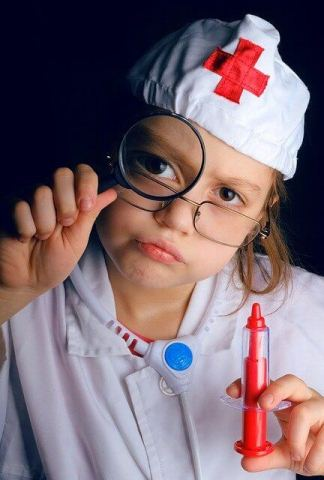 an older toddler girl in a play doctor kit - this kind of role-playing can help kids deal with their fears