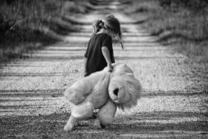 A girls with her teddy bear toy on a dirt road - toy safety for kids